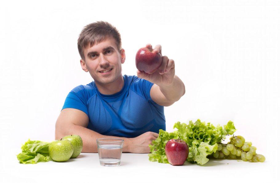 мужчина держит в руке яблоко