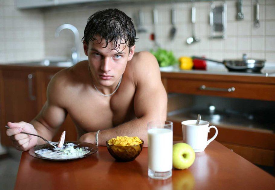 парень ест за столом