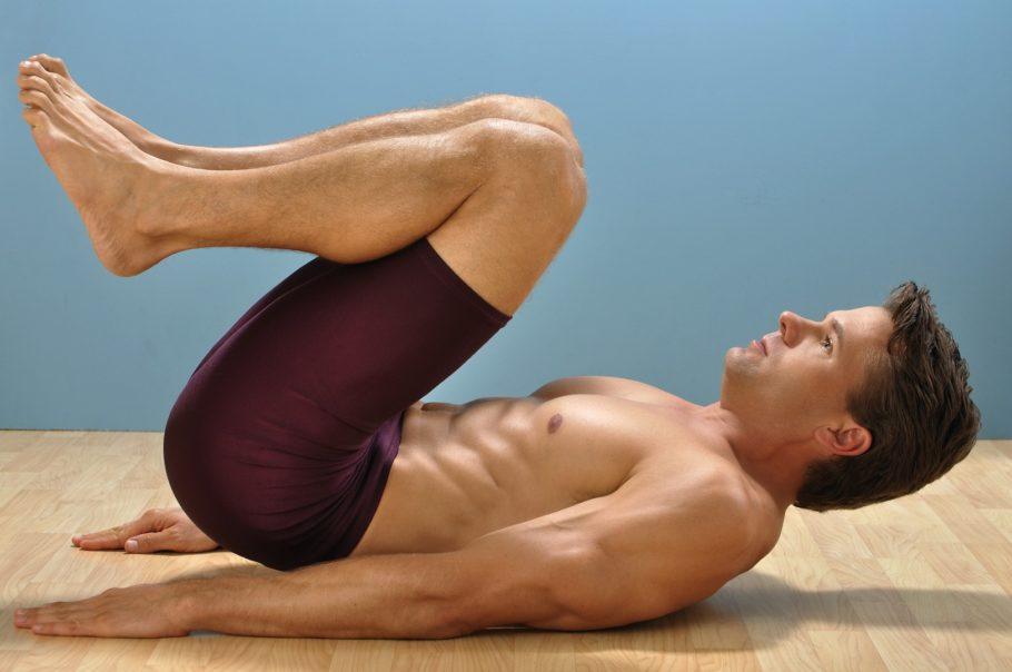 Мужчина занимается гимнастикой на полу