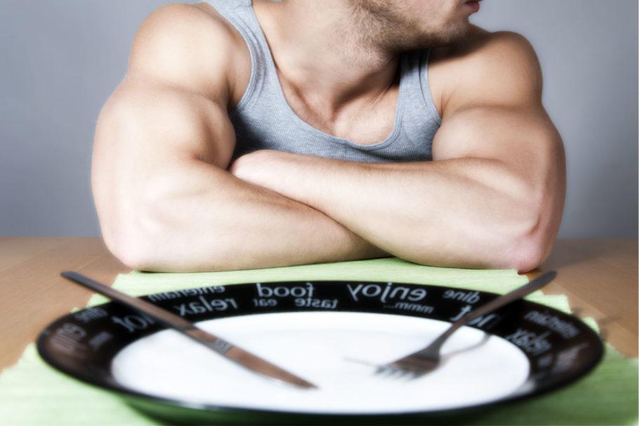 мужчина сидит напротив пустой тарелки