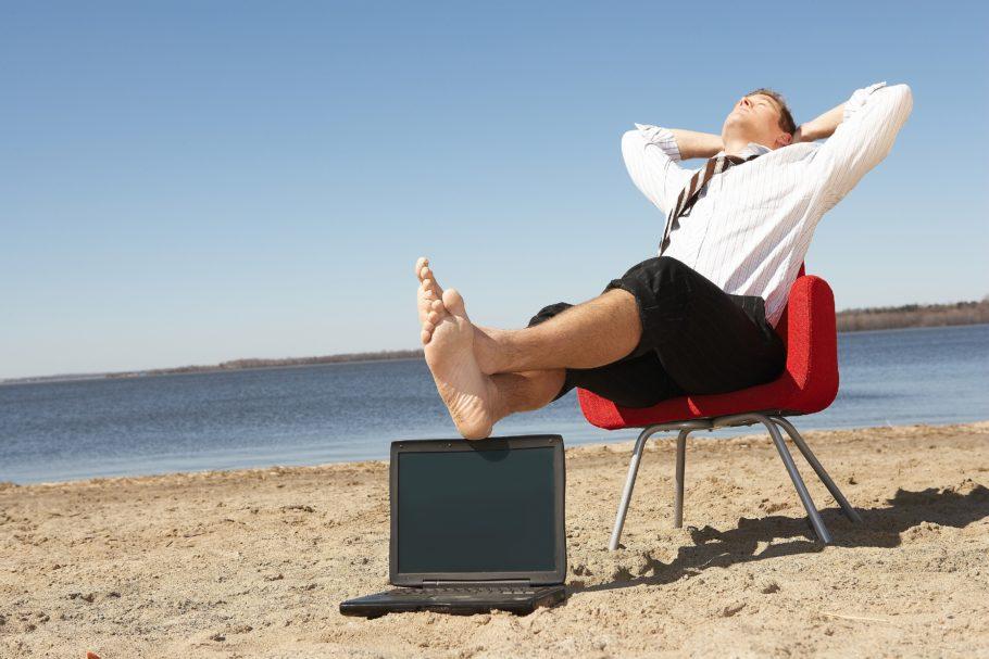 Мужчина сидит на кресле на берегу