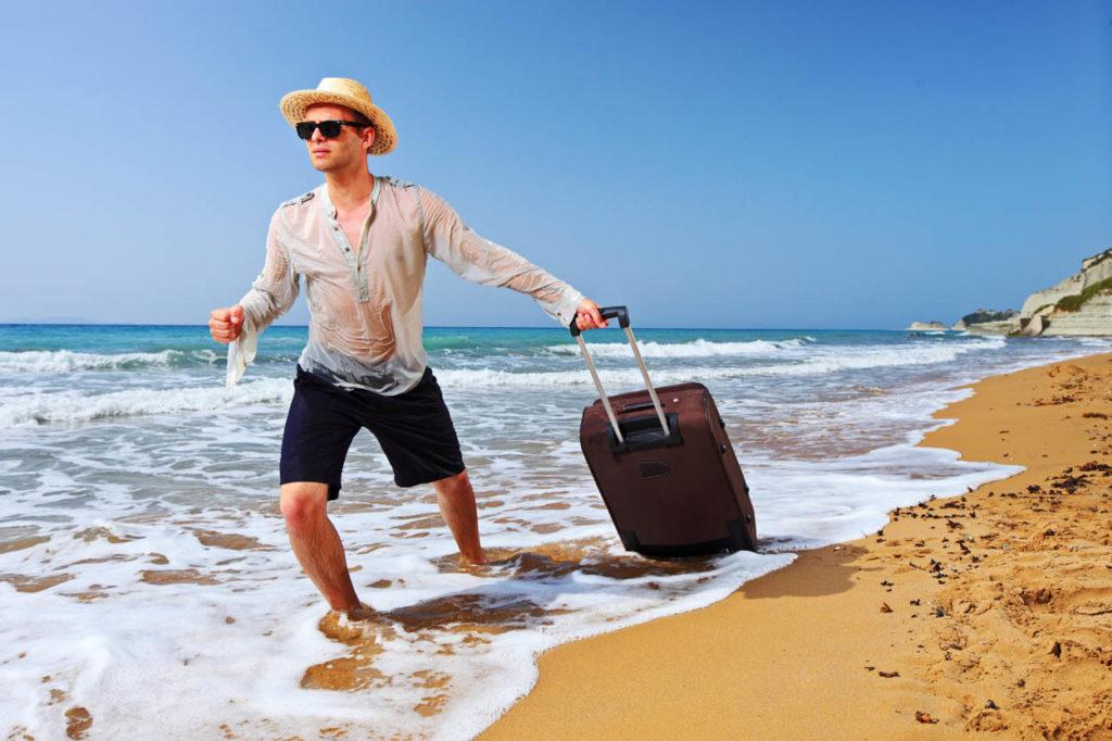 Мужчина тянет чемодан по пляжу