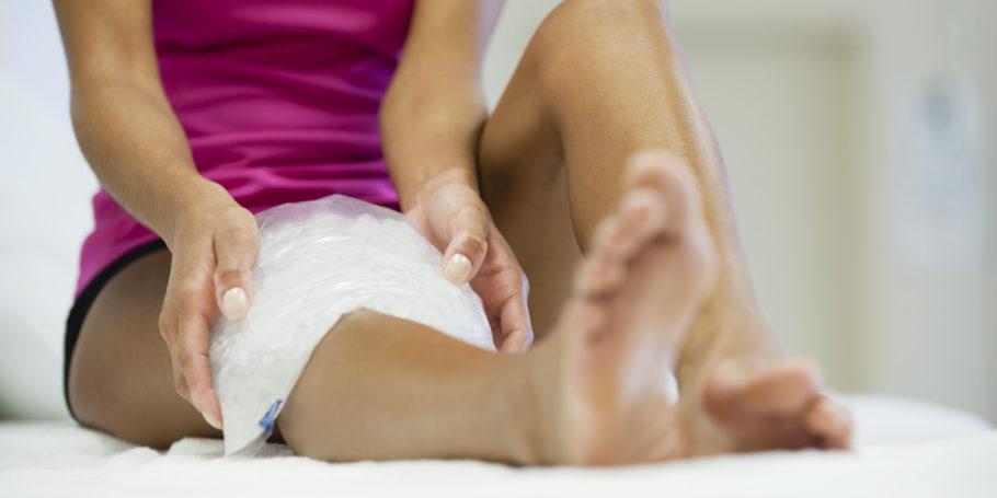 девушка прикладывает лёд к ноге