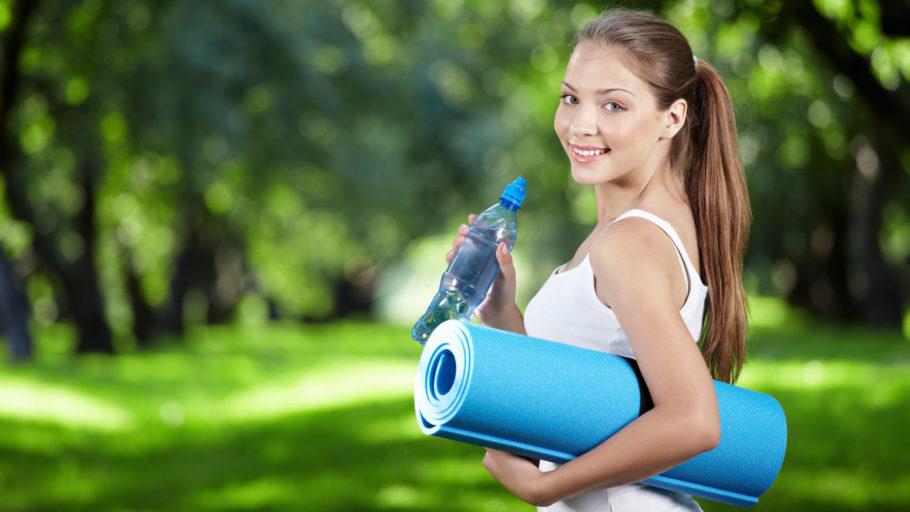 девушка с бутылкой воды и гимнастическим ковриком