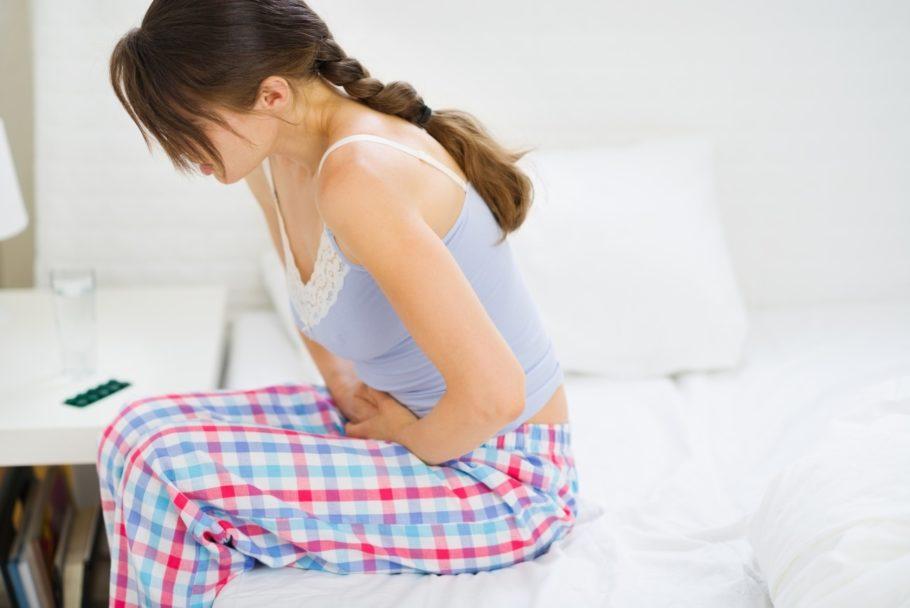 девушка с болью в животе сидит на кровати