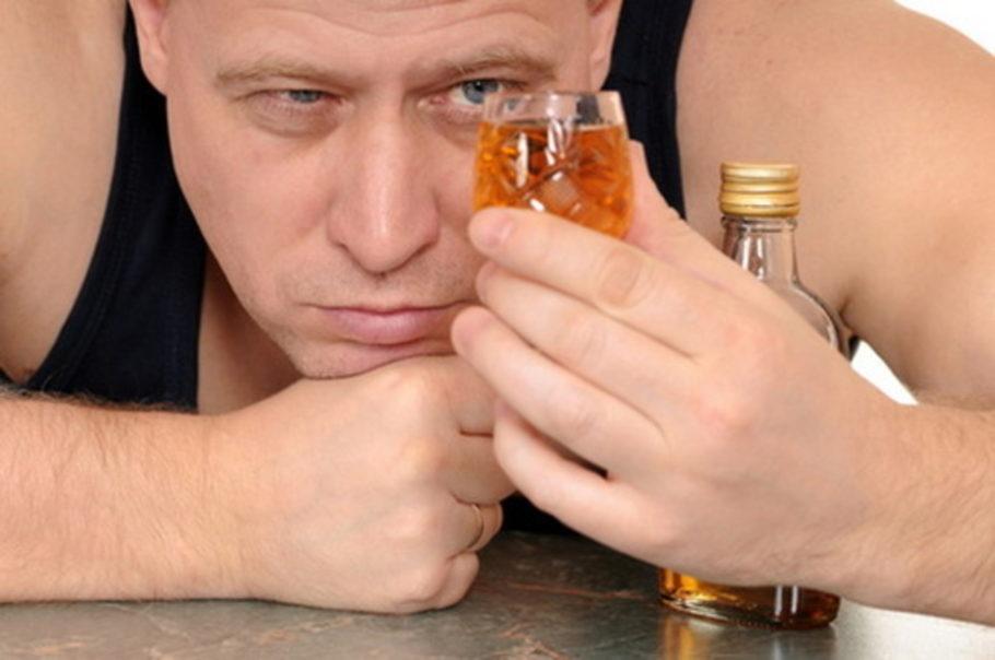 Мужчина пристально изучает рюмку со спиртным