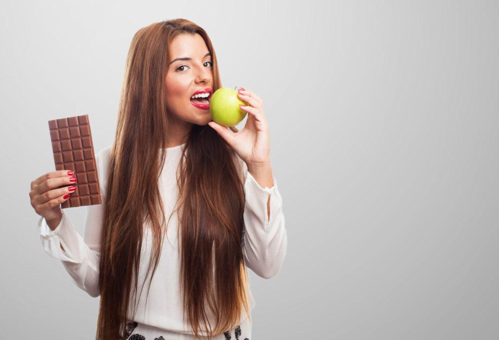 Девушка кушает яблоко и шоколад