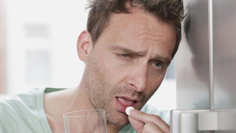 Мужчина пьет таблетку и запивает водой