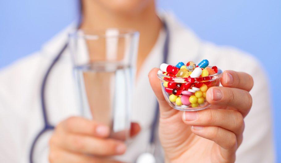 Врач держит множество таблеток