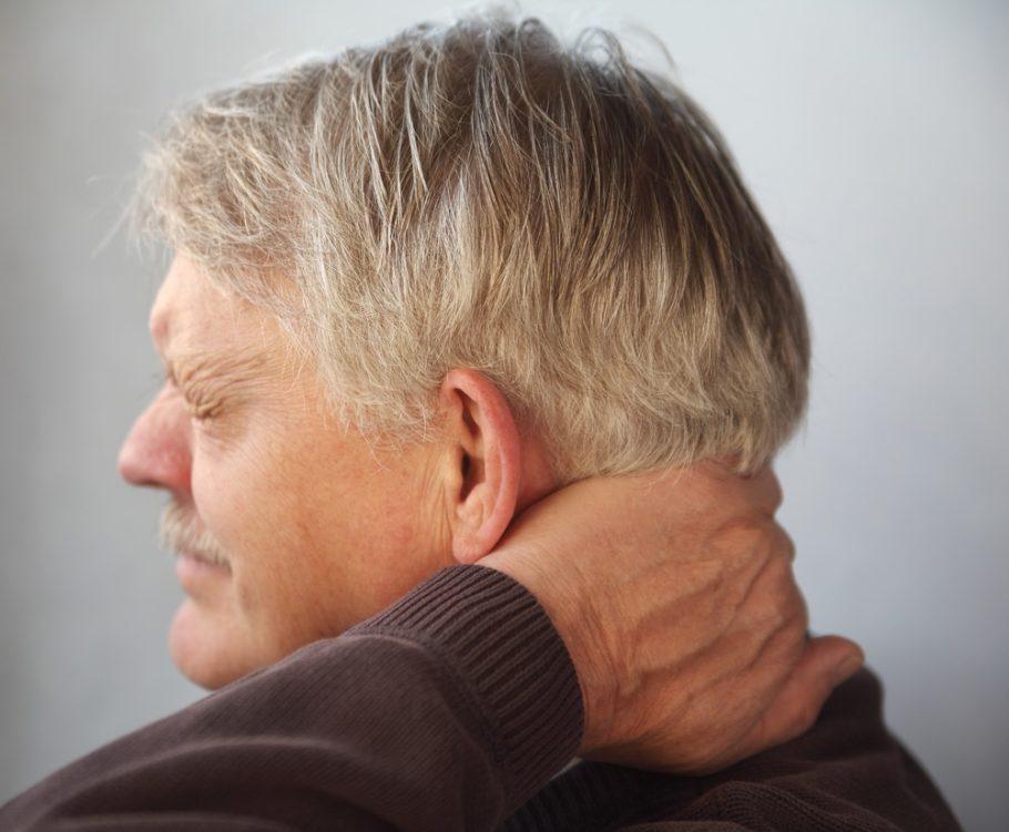 Мужчина держится рукой за шею
