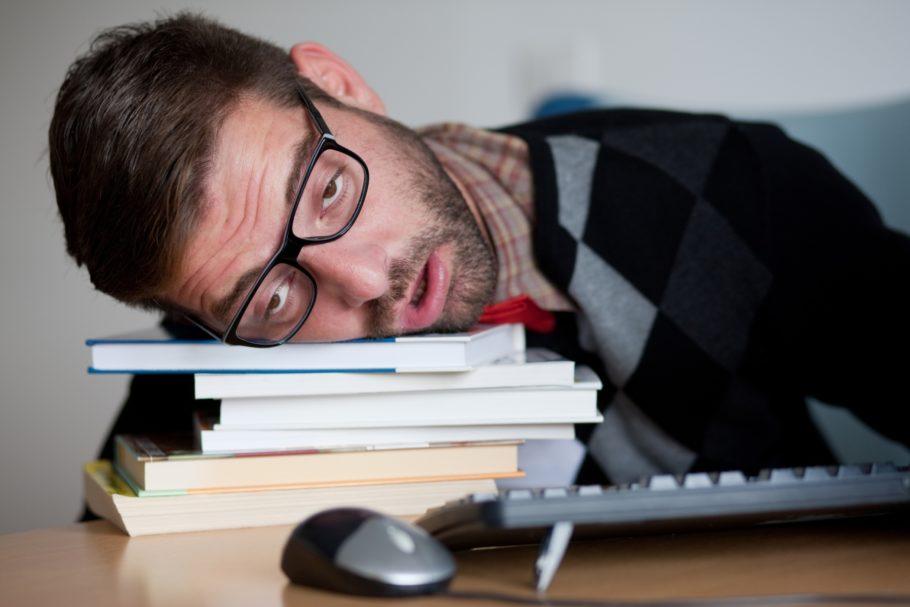 Мужчина лежит лицом на книгах