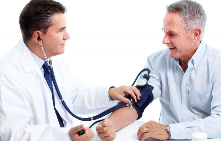 Доктор меряет давление пациенту