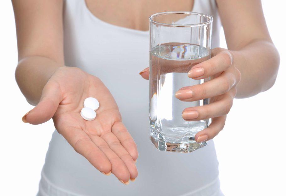 таблетки на руке и стакан с водой