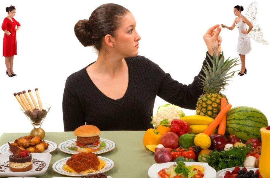 девушка за столом с полезными и вредными продуктами