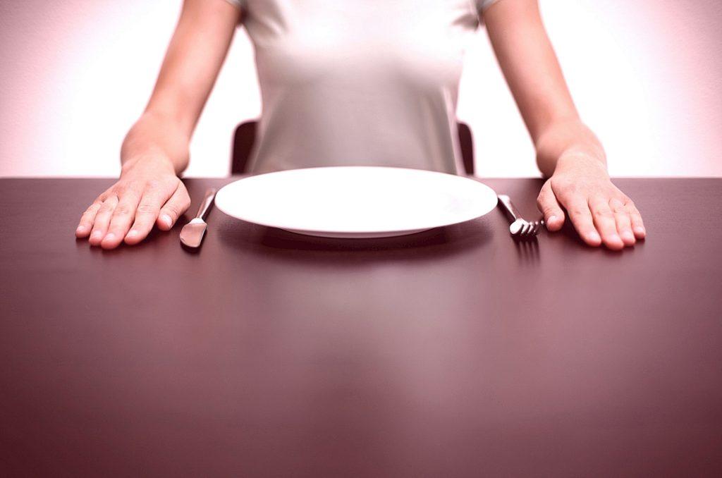 Девушка за столом с пустой тарелкой и приборами