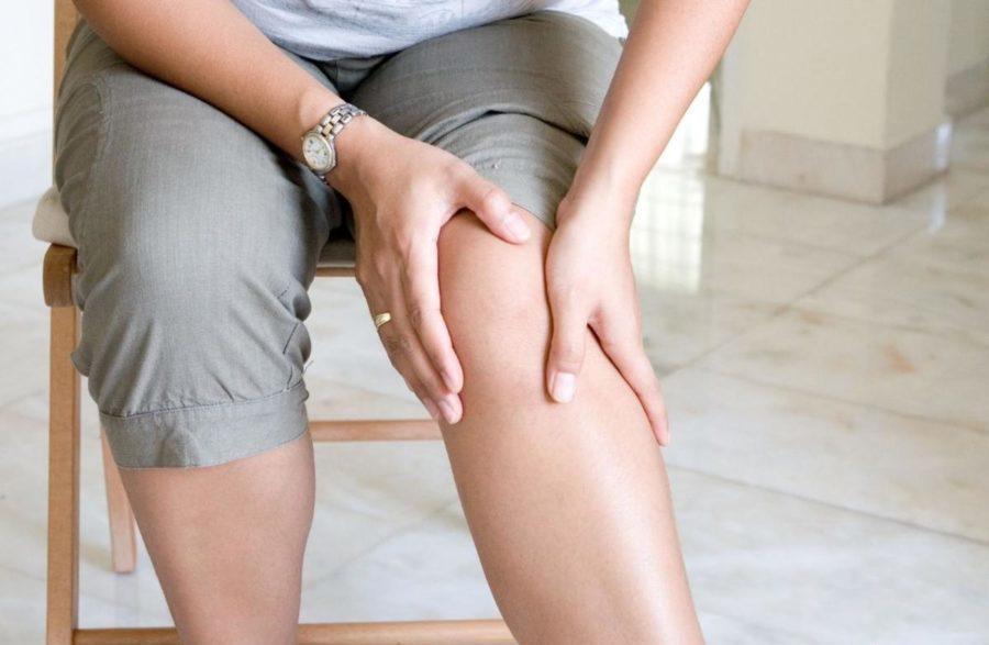 Девушка трогает руками ногу
