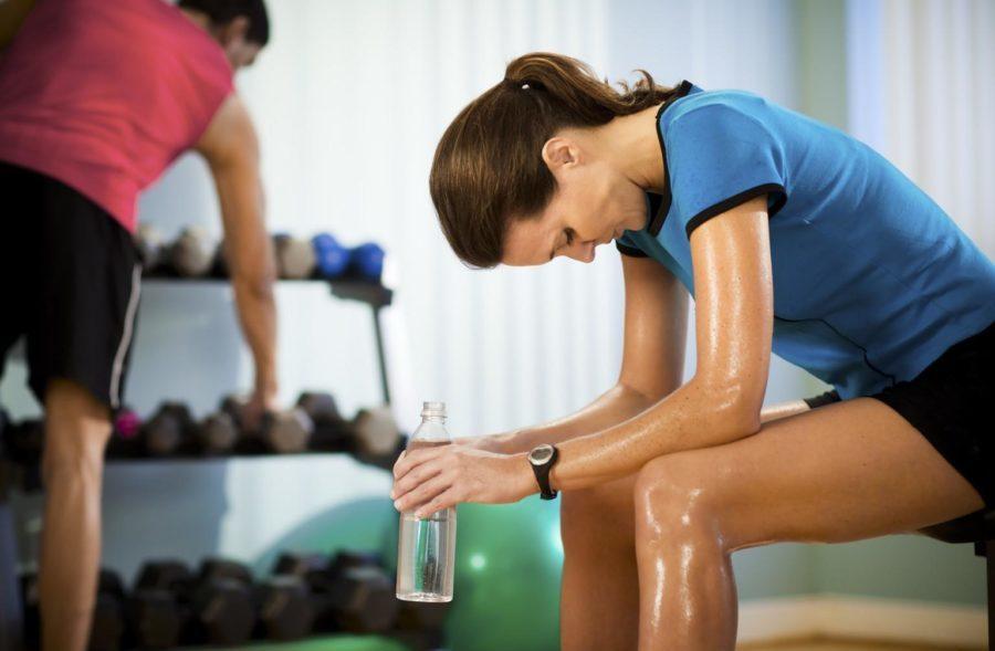 Девушка после занятий пьет воду