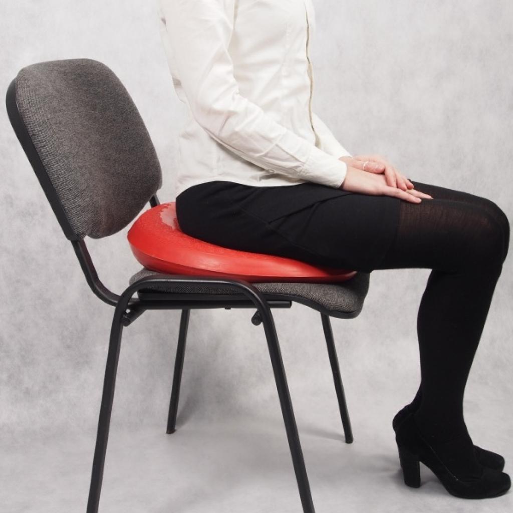 Девушка сидит на стуле с противогеморройной подушкой