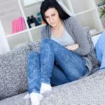 девушка на диване держится за живот