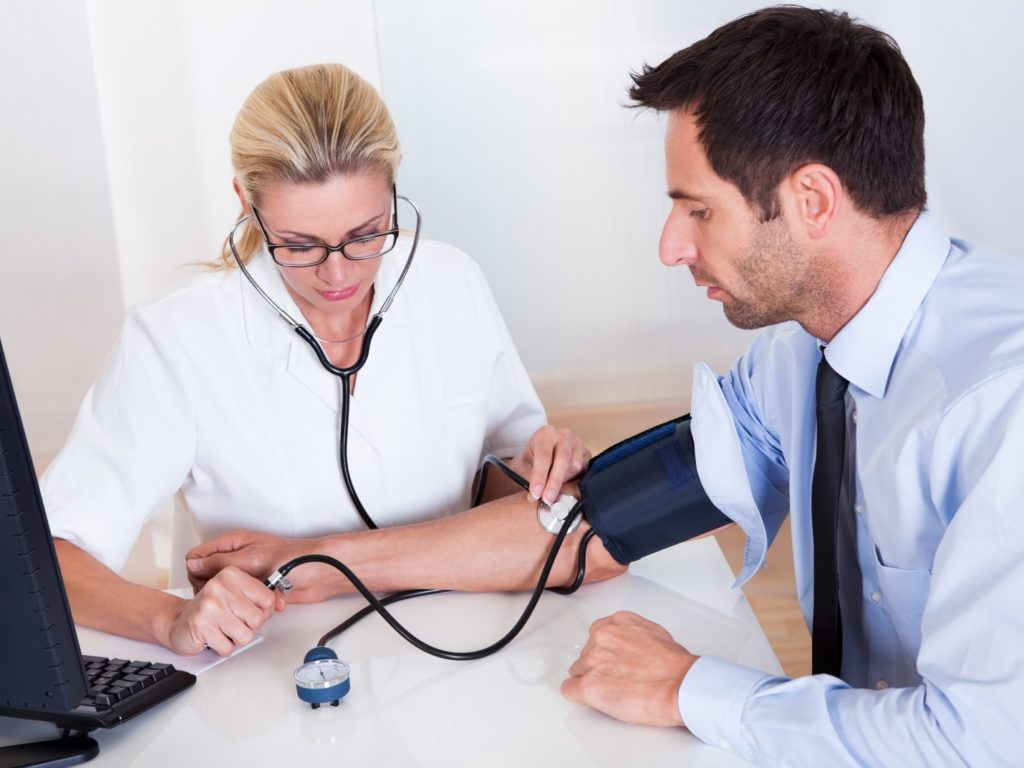 Врач меряет давление пациенту