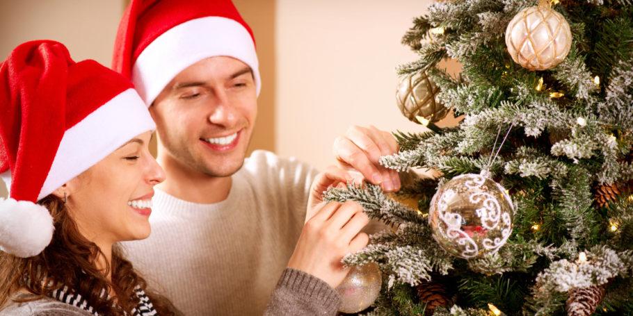 Мужчина с женщиной украшают елку