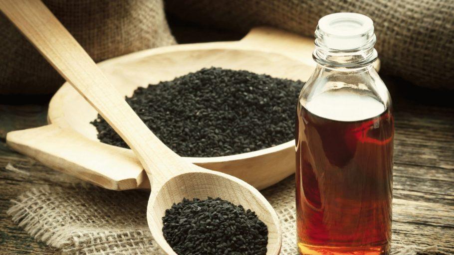 Семена черного тмина в деревянной тарелке и бутылочка с маслом