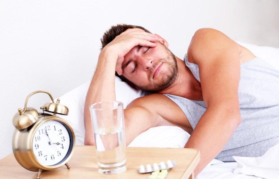 Человек испытывает алкогольное отравление, которое приводит к сильной головной боли, недомоганию, головокружению
