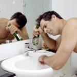 Мужчина мучается похмельем в ванной комнате с бутылкой пива в руках