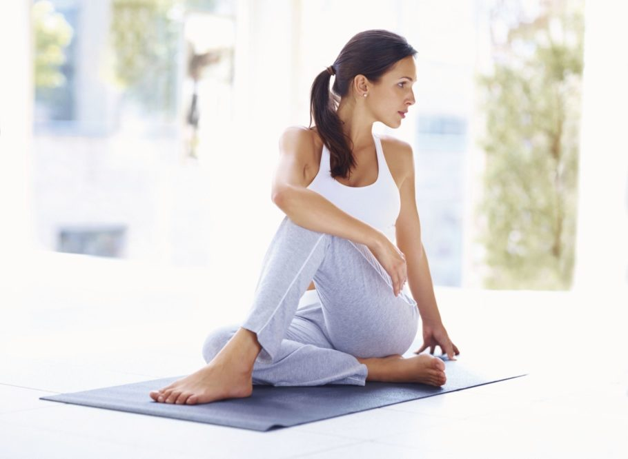 Девушка сидит на коврике для йоги