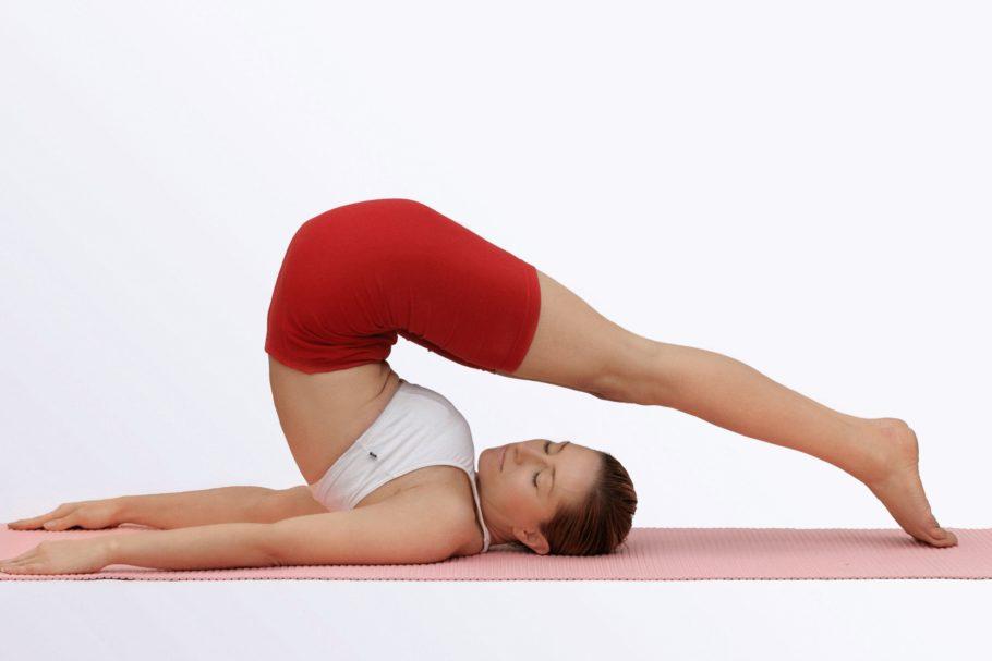 Девушка выполняет упражнение на коврике для йоги