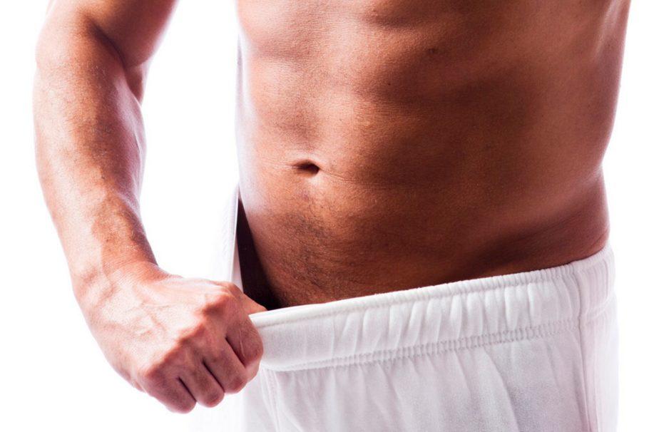 мужчина оттопыривает штаны рукой