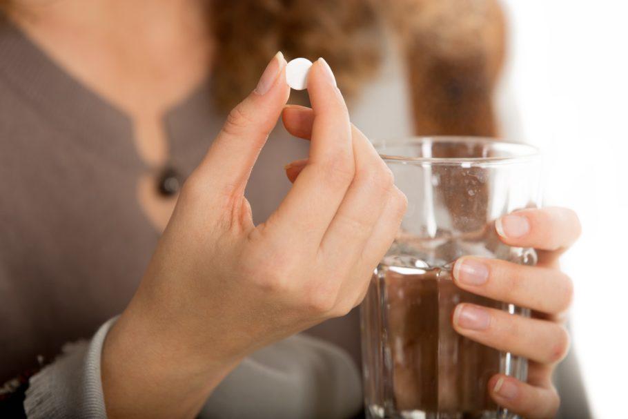 в руках таблетка и стакан с водой