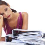 Уставшая девушка и много бумаг на столе