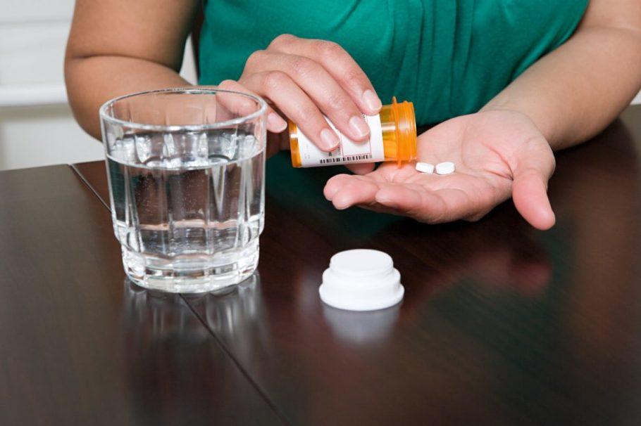 Женщина готовится принять две таблетки и запить их водой
