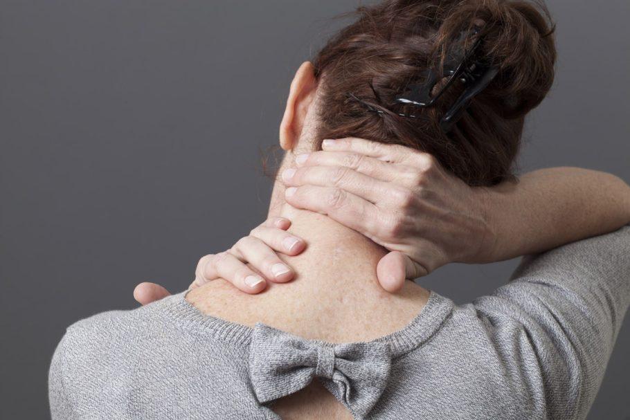 Женщина держится руками за шею