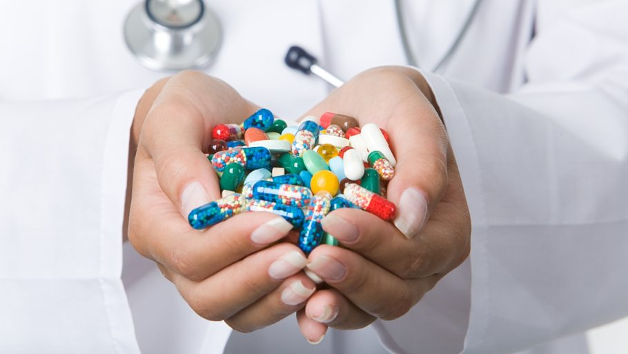 горсть разных таблеток в руках
