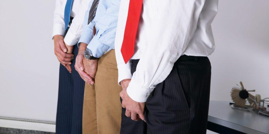 трое мужчин держатся за свой пах