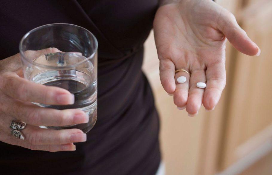 женщина держит в руках таблетки и стакан воды