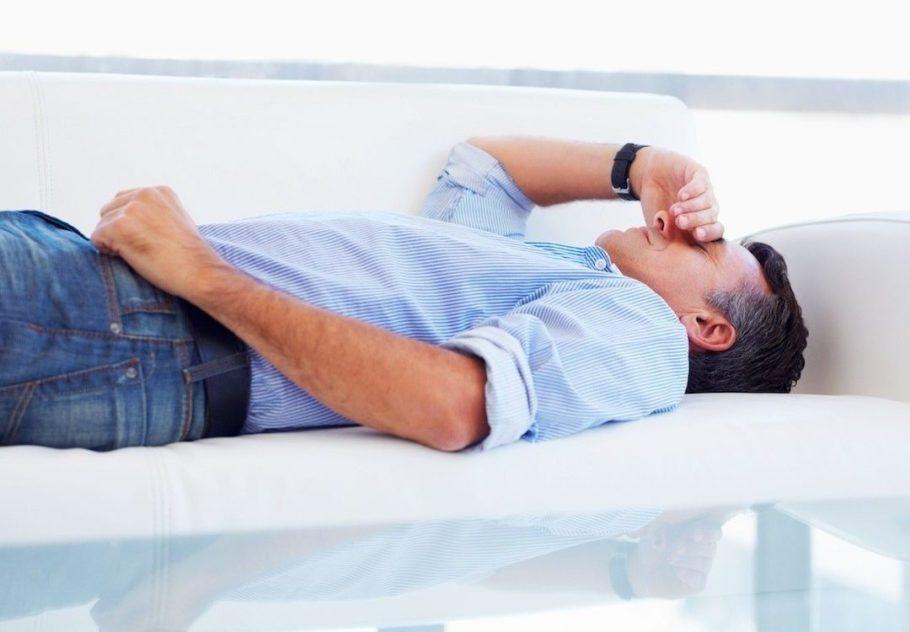 мужчина держится за голову лёжа на диване