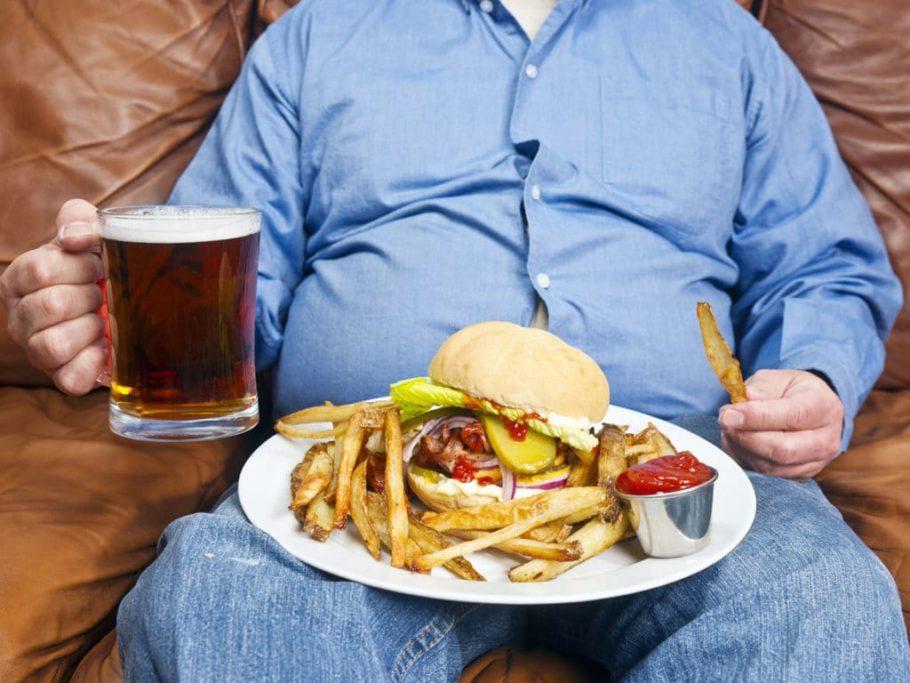 мужчина с кружкой пива и тарелкой фаст фуда