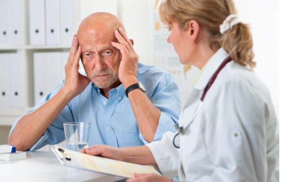 мужчина держится за голову рядом с врачом