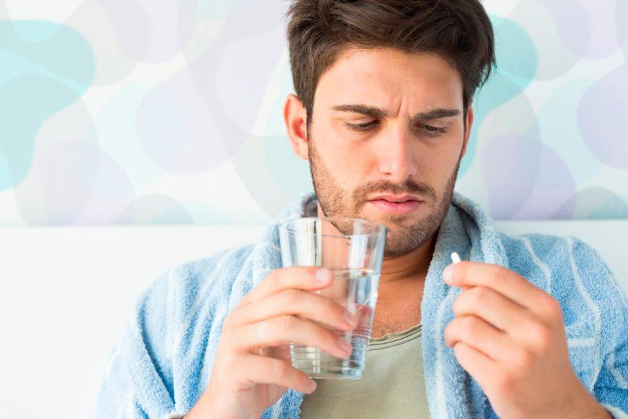 мужчина держит в руках таблетку и стакан с водой